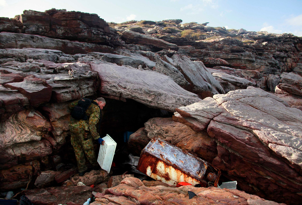 . Patrol Commander Andrew \'Dusty\' Miller, of Australia\'s North West Mobile Force (NORFORCE) unit, inspects rubbish that has washed up onto rocks on Wigram Island, part of the English Company Islands, located inside Arnhem Land in the Northern Territory, Australia July 18, 2013. NORFORCE is a surveillance unit that employs ancient Aboriginal skills to help in the seemingly impossible task of patrolling the country\'s vast northwest coast. NORFORCE\'s area of operations is about 1.8 million square km (700,000 square miles), covering the Northern Territory and the north of Western Australia. Aboriginal reservists make up a large proportion of the 600-strong unit, and bring to bear their knowledge of the land and the food it can provide. Fish, shellfish, turtle eggs and even insects supplement rations during the patrol, which is on the lookout for illegal foreign fishing vessels and drug smugglers, as well as people smugglers from neighboring Indonesia. Picture taken July 18, 2013. REUTERS/David Gray