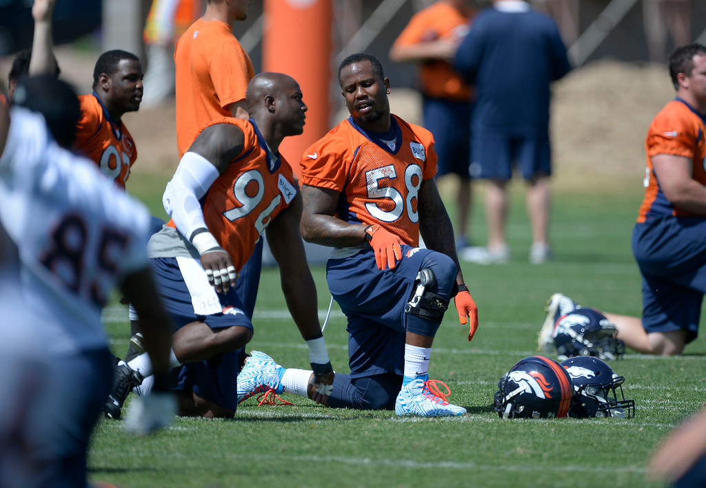 . Denver Broncos DeMarcus Ware (94) talks with Von Miller (58) as they stretch during OTAs June 11, 2014 at Dove Valley. (Photo by John Leyba/The Denver Post)