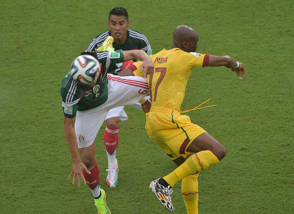 . Cameroon\'s midfielder Stephane Mbia (R) challenges Mexico\'s midfielders Hector Herrera (L) and Jose Juan Vazquez (C) during the Group A football match between Mexico and Cameroon at the Dunas Arena in Natal during the 2014 FIFA World Cup on June 13, 2014. AFP PHOTO / GABRIEL BOUYS/AFP/Getty Images