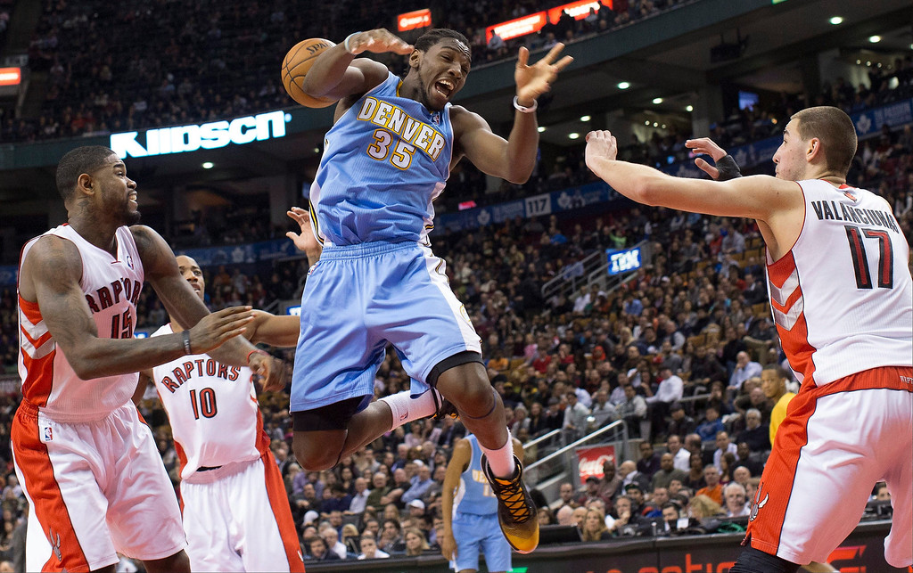 . Denver Nuggets\' Kenneth Faried (35) is fouled by Toronto Raptors\' Amir Johnson, left, as Jonas Valanciunas defends during the first half of an NBA basketball game in Toronto on Tuesday, Feb. 12, 2013. (AP Photo/The Canadian Press, Chris Young)