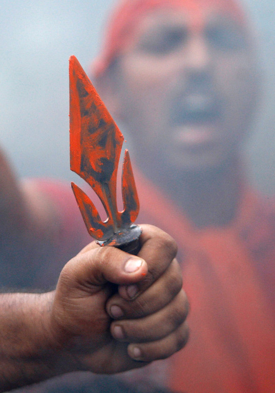 . A Hindu protestor holds a trident as another shouts slogans against the state government after rival communities clashed in Kishtwar, in Jammu, India, Saturday, Aug. 10,2013. Indian forces fired warning shots Saturday to enforce a curfew and to push angry people back into their homes in Kishtwar, in the Indian portion of Kashmir where clashes between Muslims and Hindus during Eid celebrations killed at least two people and injured another 24.(AP Photo/Channi Anand)