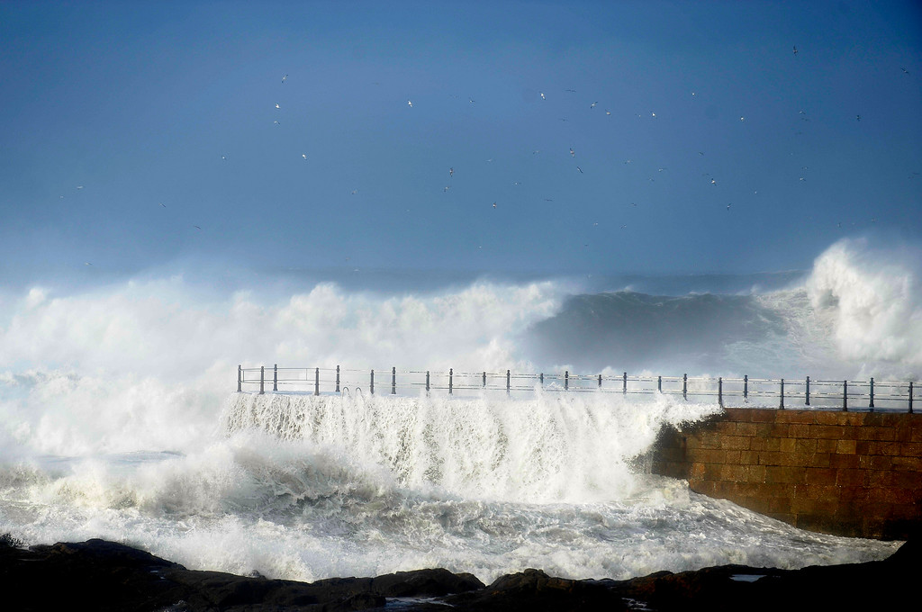 . Heavy seas and waves crash over a pier in Porto, Portugal, Tuesday, Jan. 7, 2014. Strong winds, heavy rain and rough seas caused flooding, cut off roads and damaged buildings across the entire country. (AP Photo/Paulo Duarte)