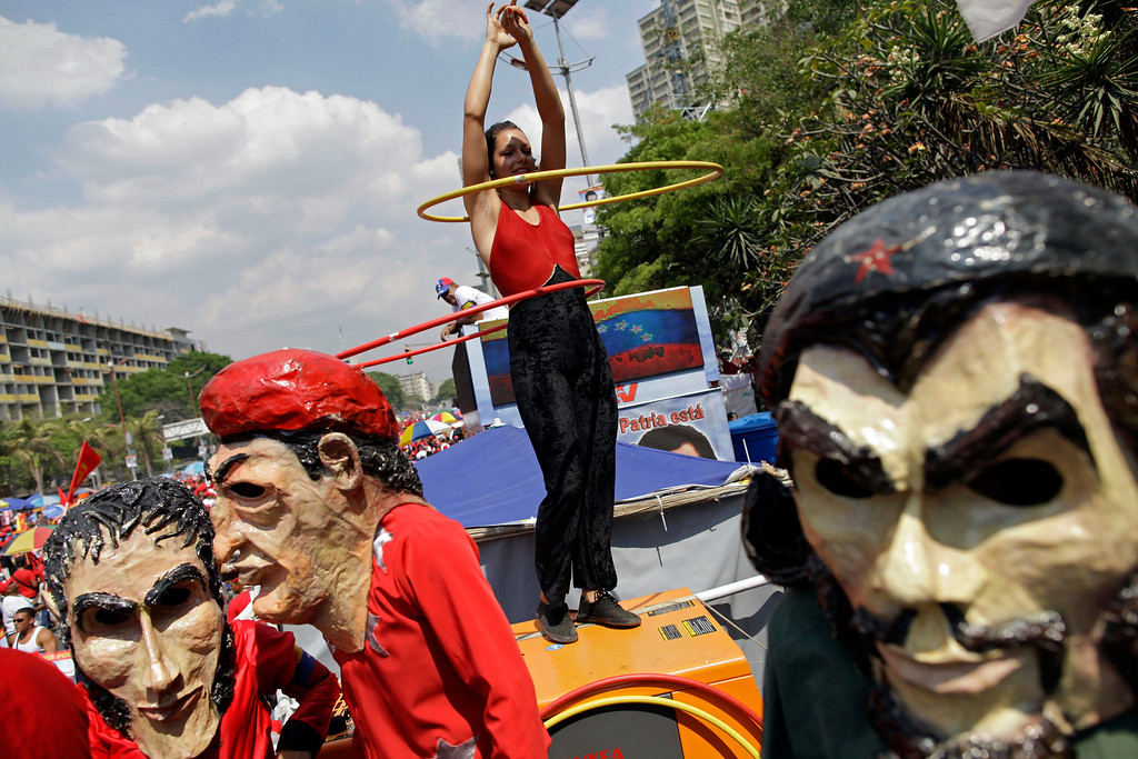 """. Supporters of ruling party presidential candidate Nicolas Maduro dressed as Cuba\'s revolutionary hero Ernesto \""""Che\"""" Guevara, right, late President Hugo Chavez, center left, and independence hero Simon Bolivar, far left, dance next to a cheerleader on a bus before Maduro\'s closing campaign rally in Caracas, Venezuela, Thursday, April 11, 2013. Maduro, Chavez\'s hand-picked successor, is running for president against opposition candidate Henrique Capriles on April 14. (AP Photo/Enric Marti)"""