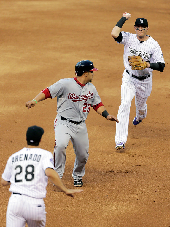 . Colorado Rockies shortstop Troy Tulowitzki, right, catches Washington Nationals baserunner Jhonatan Solano (23) in a rundown with Rockies third baseman Nolan Arenado in the third inning of a baseball game on Wednesday, June 12, 2013 in Denver. Solano was put out by Arenado. (AP Photo/Joe Mahoney)