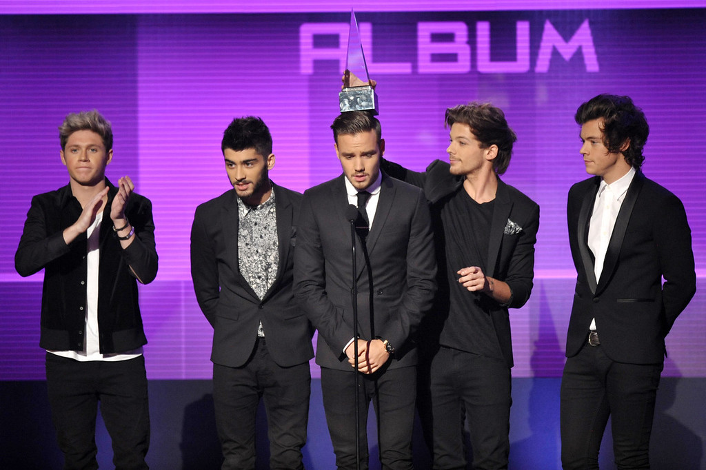 ". From left, Niall Horan, Zayn Malik, Liam Payne, Louis Tomlinson, and Harry Styles of musical group One Direction, accept the award for favorite album - pop/rock for ""Take Me Home\"" at the American Music Awards at the Nokia Theatre L.A. Live on Sunday, Nov. 24, 2013, in Los Angeles. (Photo by John Shearer/Invision/AP)"