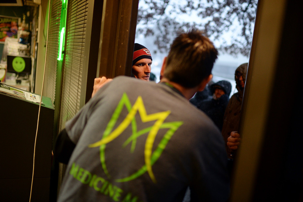 . DENVER, CO. JANUARY 01: Medicine man chief operating officer Pete Williams, front, checks in their first customer Tony Muhle from Bennett, CO., left, before fully opening the door. People stood in lines for hours to buy legal marijuana at Medicine Man marijuana dispensary on the morning of New Years day in Denver, Colorado January 1, 2014. (Photo by Hyoung Chang/The Denver Post)