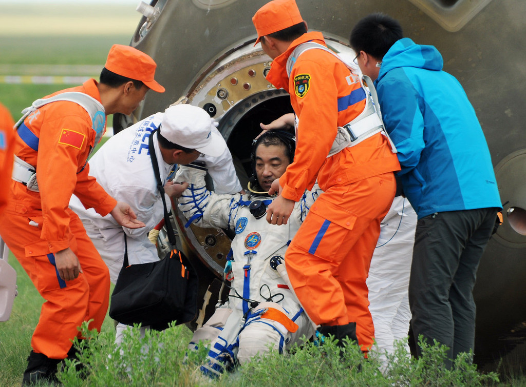 . Chinese astronaut Zhang Xiaoguang (C) is helped by technicians to get out from the Shenzhou-10 spacecraft after it landed in the grasslands of north China\'s Inner Mongolia region on June 26, 2013, following a 15-day mission in space. China completed its longest manned space mission on June 26 as its Shenzhou-10 spacecraft and three crew members safely returned to Earth, in a major step towards Beijing\'s goal of building a permanent space station by 2020.  AFP PHOTOAFP/AFP/Getty Images
