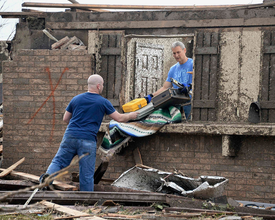 . People salvage belongings after a huge tornado struck Moore, Oklahoma May 20, 2013. A 2-mile-wide (3-km-wide) tornado tore through the Oklahoma City suburb of Moore on Monday, killing at least 51 people while destroying entire tracts of homes, piling cars atop one another, and trapping two dozen school children beneath rubble. REUTERS/Gene Blevins