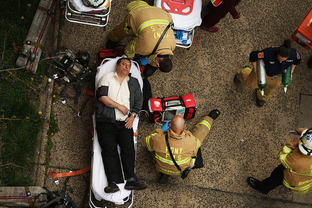 . An injured man is aided by New York City firefighters after being evacuated from an emergency staircase following an F train derailment on May 2, 2014 in the Woodside neighborhood of the Queens borough in New York City. According to the Metropolitan Transportation Authority  (MTA) the express F train was bound for Manhattan and Brooklyn when it derailed at 10:40 a.m. about 1,200 feet from the 65th station in Woodside, Queens with hundreds of passengers on board.  (Photo by Spencer Platt/Getty Images)