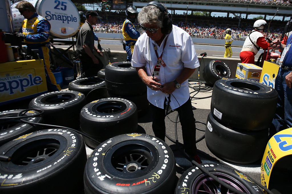 . Mario Andretti looks over the tires of Marco Andretti, driver of the #25 Snapple Andretti Autosport Honda Dallara, during the 98th running of the Indianapolis 500 Mile Race at Indianapolis Motorspeedway on May 25, 2014 in Indianapolis, Indiana.  (Photo by Chris Graythen/Getty Images)