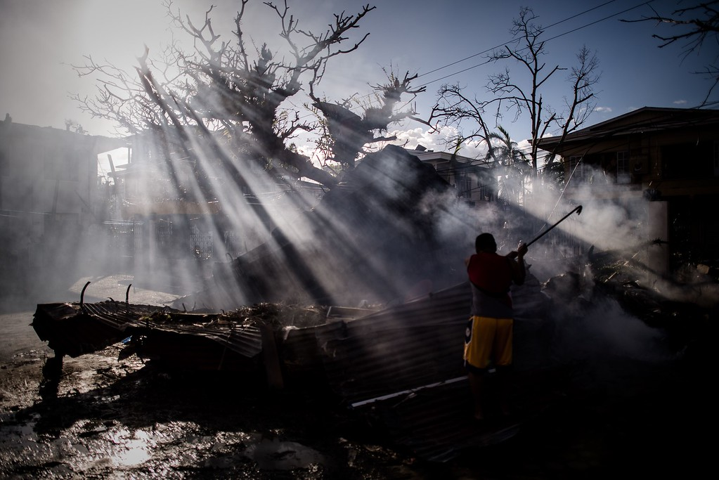 . A man cleans up debris from a courtyard on the 7th day of the Typhoon Haiyan disaster in Tacloban, on the eastern island of Leyte on November 15, 2013. AFP PHOTO/Philippe LOPEZ/AFP/Getty Images