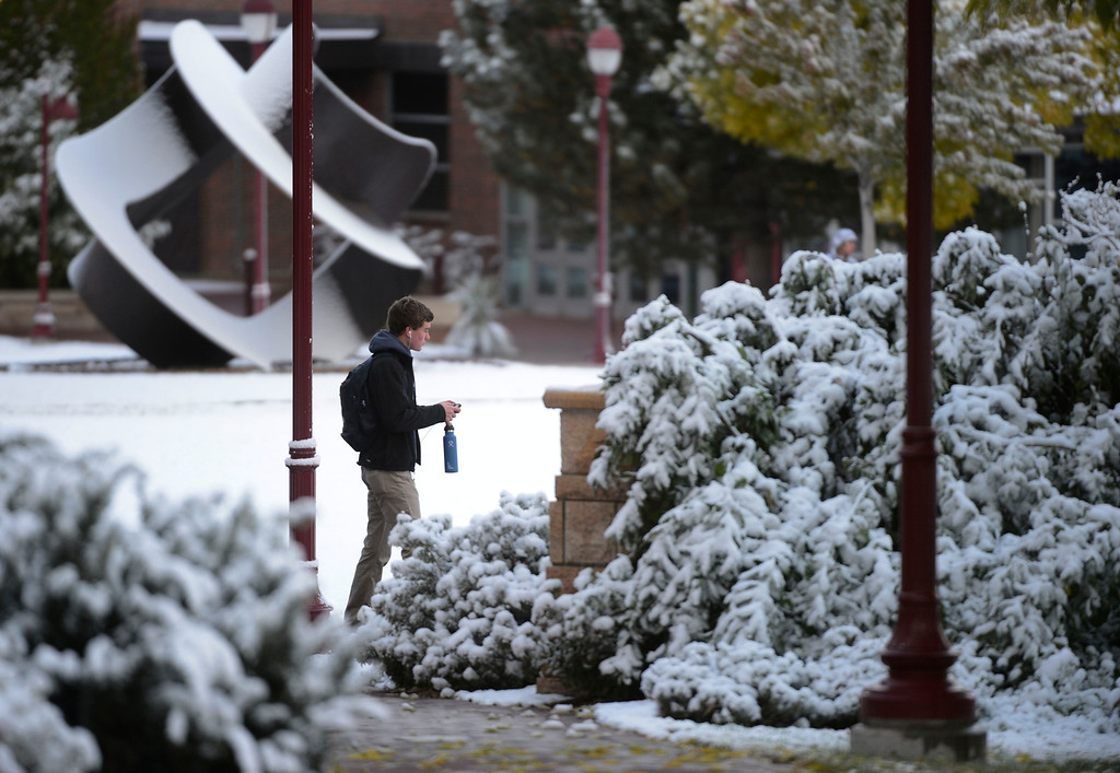 . A man walks through the University of Denver campus in a fresh blanket of snow Friday morning, October 18, 2013. (Photo By Andy Cross/The Denver Post)