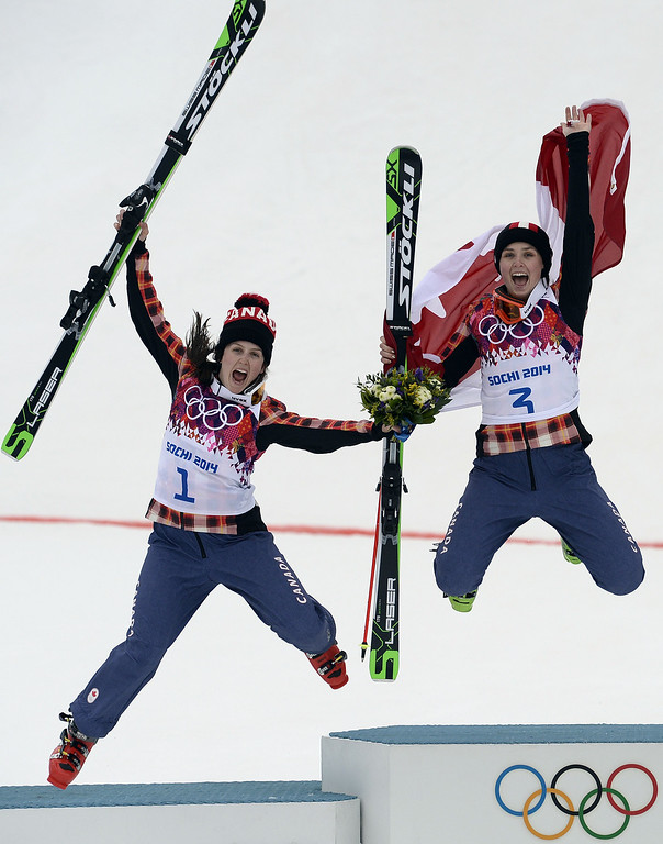 . Canada\'s silver medallist Kelsey Serwa (L) and Canada\'s gold medal winner Marielle Thompson jump in the air as they celebrate at the Women\'s Freestyle Skiing Ski Cross Flower Ceremony at the Rosa Khutor Extreme Park during the Sochi Winter Olympics on February 21, 2014. AFP PHOTO / FRANCK  FIFE/AFP/Getty Images