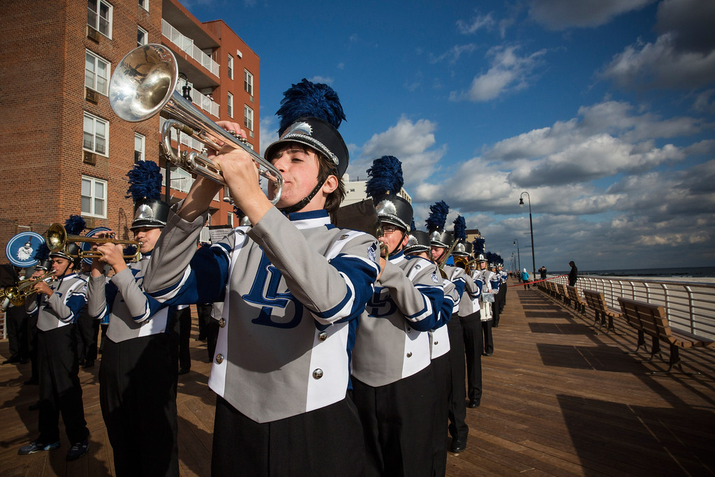 . LONG BEACH, NY - OCTOBER 25:  A member of the Long Beach High School marching band plays trumpet while marching down the Long Beach boardwalk during a ceremony to officially reopen the boardwalk on October 25, 2013 in Long Beach, New York. The boardwalk was severely damaged by Superstorm Sandy last year, which killed 285 people and caused billions of dollars in damage. Long Beach\'s new boardwalk is made of Brazilian hardwood and is estimated to have a lifespan of 30-40 year; the previous boardwalk was only scheduled to last  three to seven years.  (Photo by Andrew Burton/Getty Images)