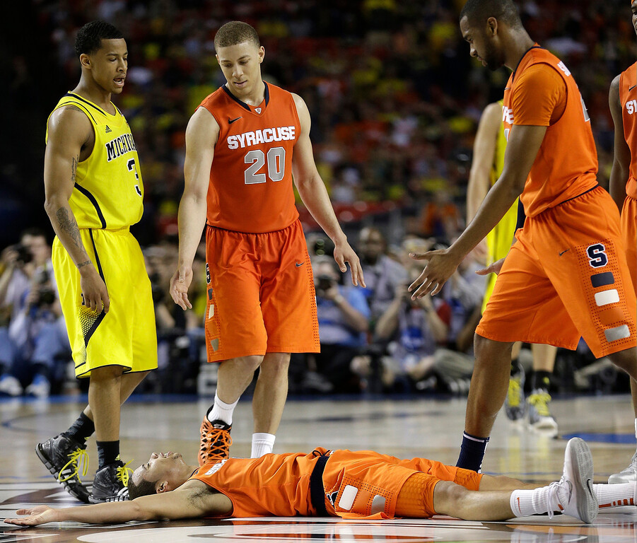 . Syracuse\'s Michael Carter-Williams (1) lies on the court as Syracuse\'s Brandon Triche (20) helps him during the second half of the NCAA Final Four tournament college basketball semifinal game against Michigan, Saturday, April 6, 2013, in Atlanta. (AP Photo/John Bazemore)