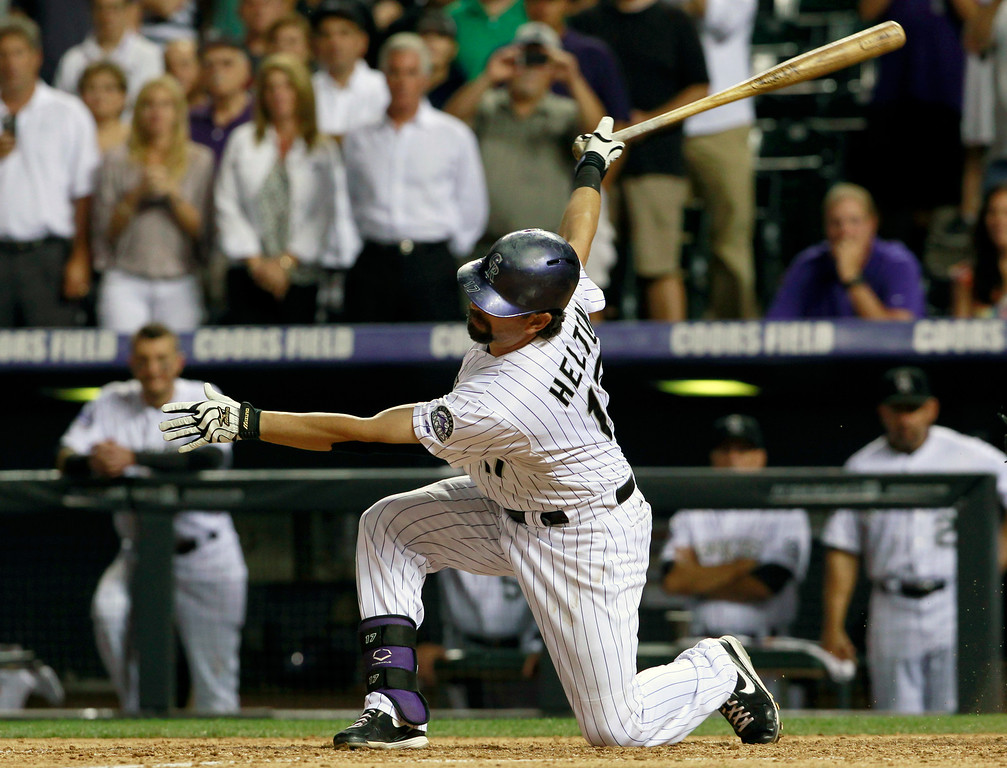 . Colorado Rockies\' Todd Helton swings at a pitch on the way to striking out against the Cincinnati Reds in the ninth inning of the Reds\' 8-3 victory in a baseball game in Denver on Saturday, Aug. 31, 2013. Helton was hitless in four at-bats in the game as he pursues the 2,500th hit in his career. (AP Photo/David Zalubowski)