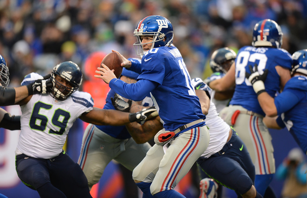 . Quarterback Eli Manning #10 of the New York Giants under pressure as he throws during the 2nd half of the Seattle Seahawks 23-0 win over the New York Giants at MetLife Stadium on December 15, 2013 in East Rutherford, New Jersey. (Photo by Ron Antonelli/Getty Images)