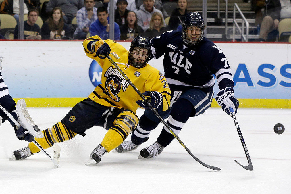 . Quinnipiac\'s Matthew Peca (20) and Yale\'s Matt Killian (7) go after a rebound during the first period of the NCAA Frozen Four men\'s college hockey national championship game in Pittsburgh on Saturday, April 13, 2013. (AP Photo/Gene Puskar)