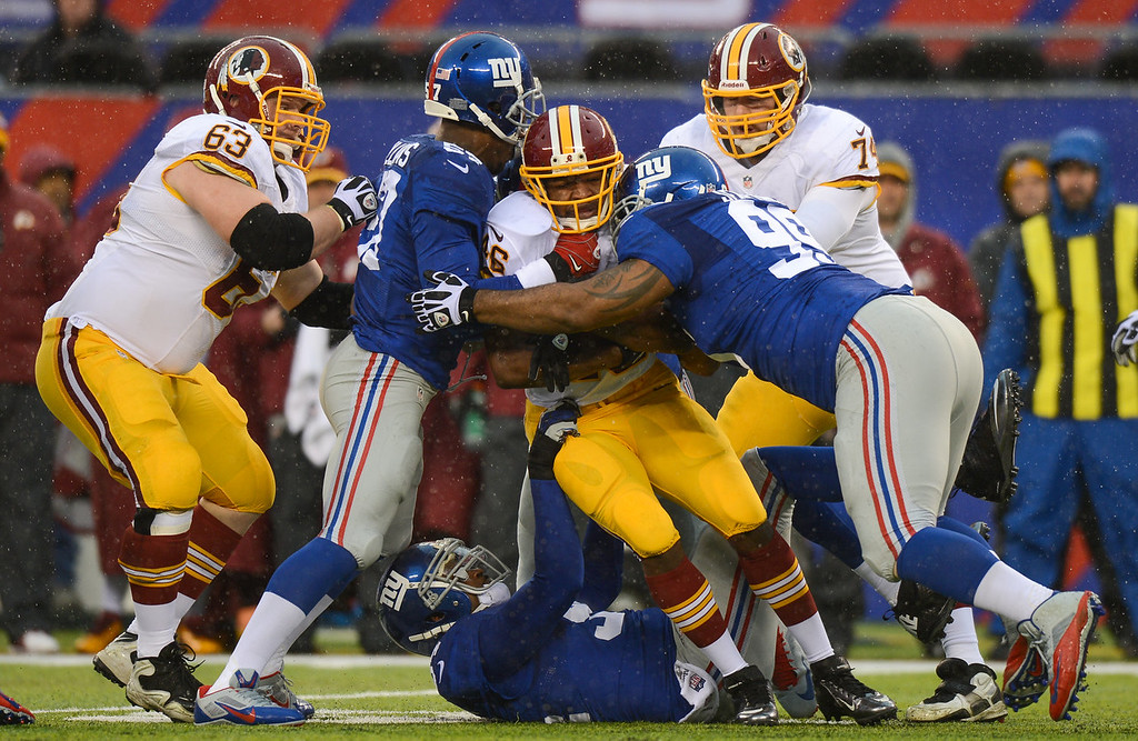 . Running back Alfred Morris #46 of the Washington Redskins is tackled by outside linebacker Jacquian Williams #57  and defensive tackle Cullen Jenkins #99 of the New York Giants in the first half  at MetLife Stadium on December 29, 2013 in East Rutherford, New Jersey. (Photo by Ron Antonelli/Getty Images)