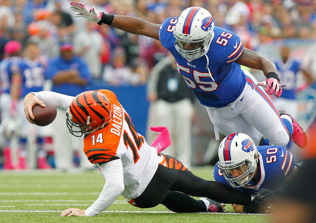 . Cincinnati Bengals quarterback Andy Dalton (14) stretches for more yardage as Buffalo Bills outside linebacker Jerry Hughes (55) dives towards him in the first quarter of the NFL football game on Sunday, Oct. 13, 2013, in Orchard Park, N.Y. (AP Photo/Bill Wippert)