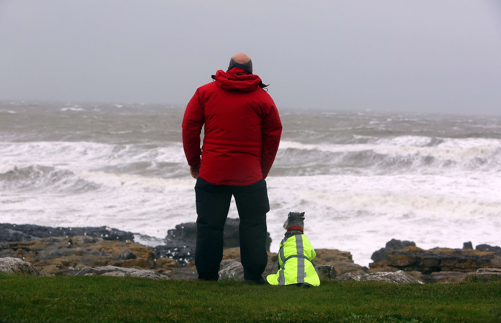 . A man and his dog stand watching as waves roll in at the beach in Porthcawl, south Wales on October 27, 2013 ahead of the arrival of a predicted storm. Britain was braced on October 27 for its worst storm in a decade, with heavy rain and winds of more than 80 miles (130 kilometres) an hour set to batter the south of the country.    GEOFF CADDICK/AFP/Getty Images