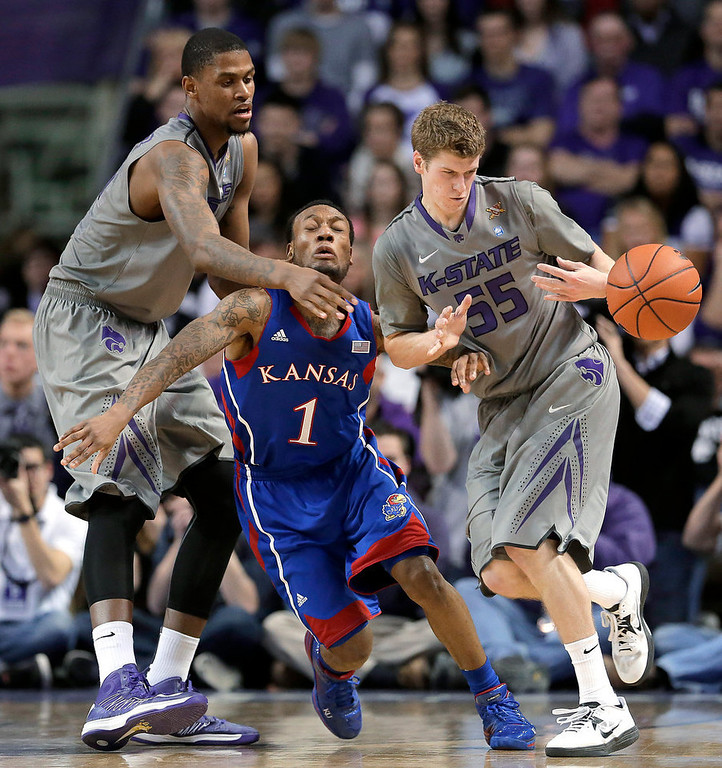 . Kansas State forward Jordan Henriquez, left, and guard Will Spradling (55) and Kansas guard Naadir Tharpe (1) vie for a loose ball during the first half of an NCAA college basketball game Tuesday, Jan. 22, 2013, in Manhattan, Kan. (AP Photo/Charlie Riedel)