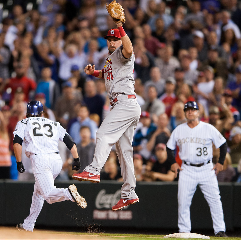 . Brock Peterson #41 of the St. Louis Cardinals leaps to catch an errant throw as Charlie Culberson #23 of the Colorado Rockies beats out the throw in the ninth inning of a game at Coors Field on September 18, 2013 in Denver, Colorado. (Photo by Dustin Bradford/Getty Images)