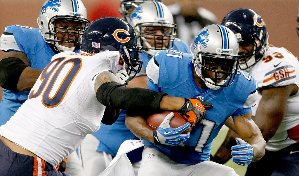 . DETROIT, MI - SEPTEMBER 29: Julius Peppers #90 of the Chicago Bears grabs a hold of Reggie Bush #21 of the Detroit Lions at Ford Field on September 29, 2013 in Detroit, Michigan. (Photo by Gregory Shamus/Getty Images)
