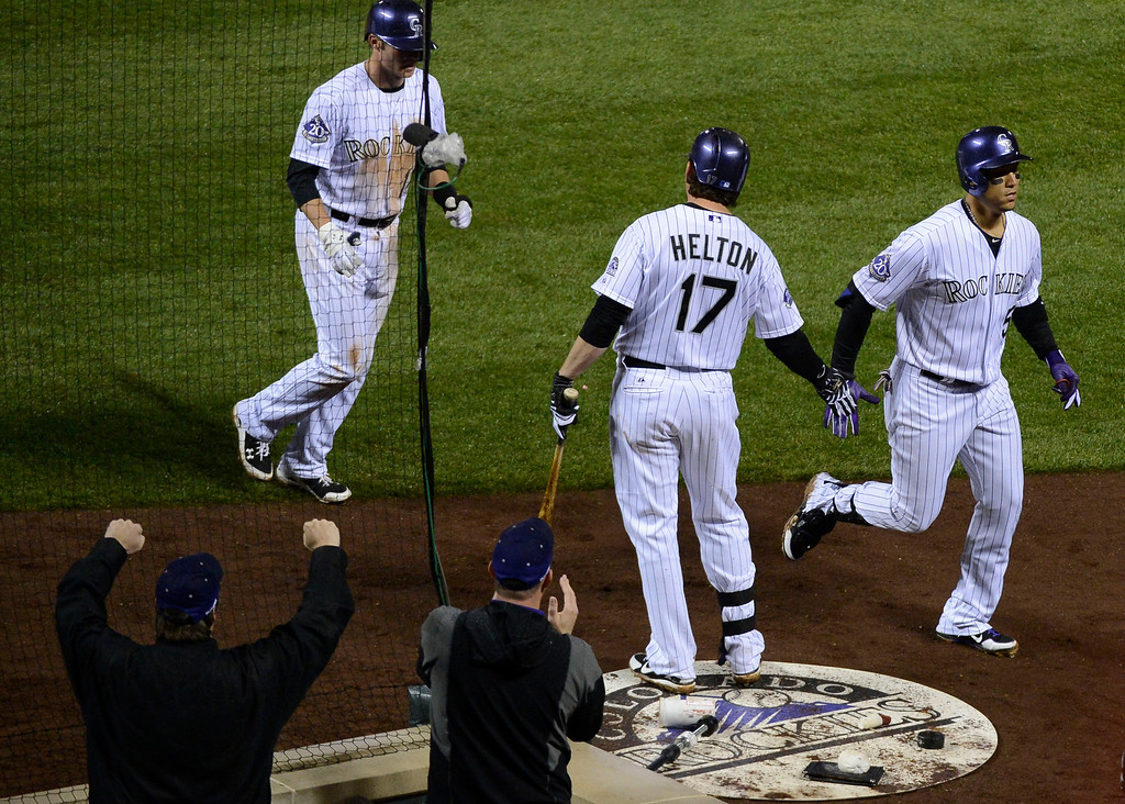 . DENVER, CO. - MAY 07: Carlos Gonzalez (5) of the Colorado Rockies is congratulated by Todd Helton (17) after hitting a two run home run scoring Josh Rutledge (14) in the sixth inning against the New York Yankees May 7, 2013 at Coors Field. (Photo By John Leyba/The Denver Post)