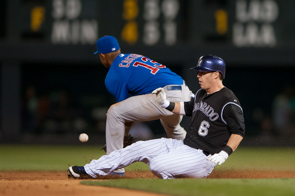 . DENVER, CO - AUGUST 06:  Corey Dickerson #6 of the Colorado Rockies slides into second base with a hustled double as Starlin Castro #13 of the Chicago Cubs takes the throw from the outfield in the sixth inning of a game at Coors Field on August 6, 2014 in Denver, Colorado.  (Photo by Dustin Bradford/Getty Images)