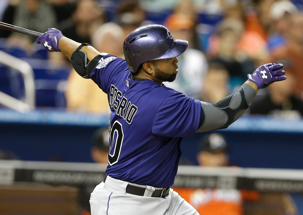 . Colorado Rockies\' Wilin Rosario hits a single during the fourth inning of an opening day baseball game against the Miami Marlins, Monday, March 31, 2014, in Miami. (AP Photo/Lynne Sladky)
