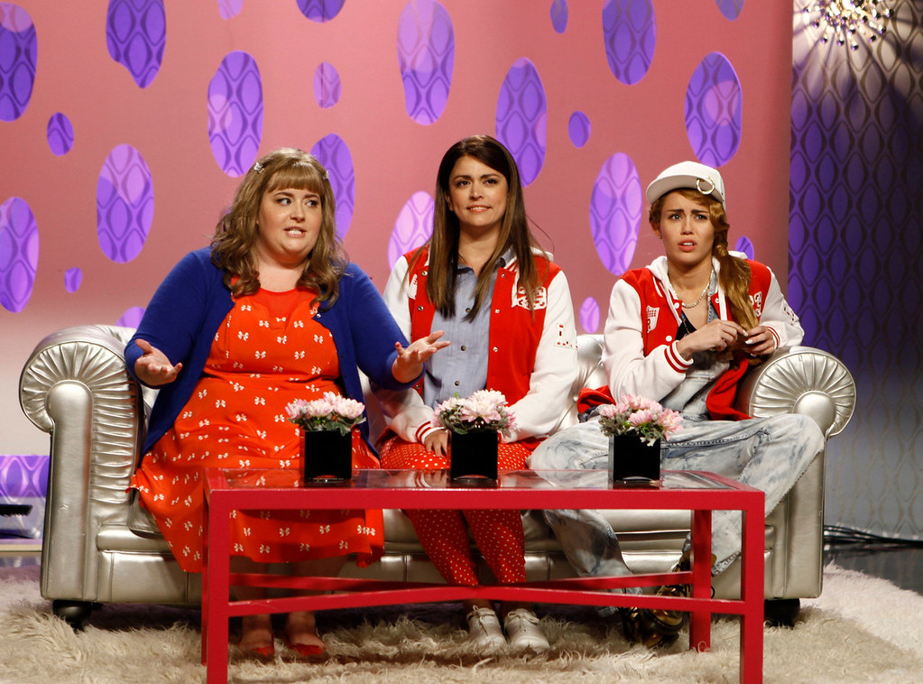 """. From left, Aidy Bryant, Cecily Strong, and guest host Miley Cyrus in a scene from the late-night comedy series \""""Saturday Night Live,\"""" in New York on Oct. 5, 2013. (AP Photo/NBC, Dana Edelson)"""