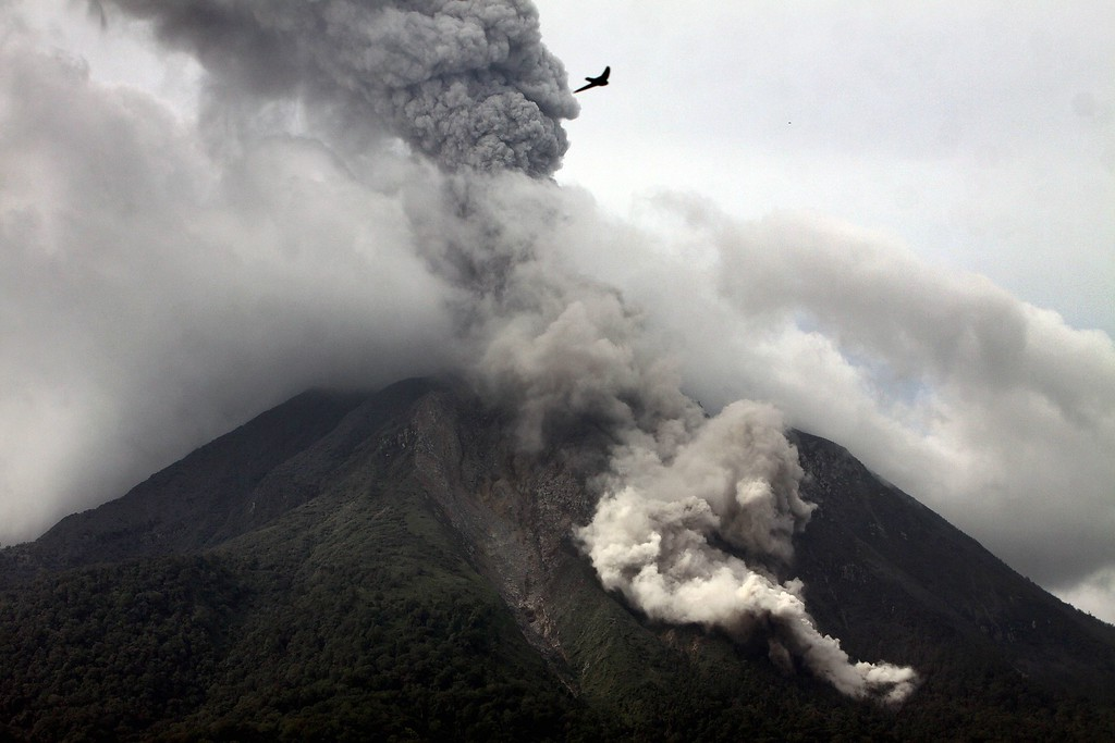 . A plume of steam and ash rises as lava rolls from the crater of the Mount Sinabung volcano during an eruption as seen from the Karo district on the Indonesian island of Sumatra on November 5, 2013.   AFP PHOTO / KARISHMA TARIGAN/AFP/Getty Images