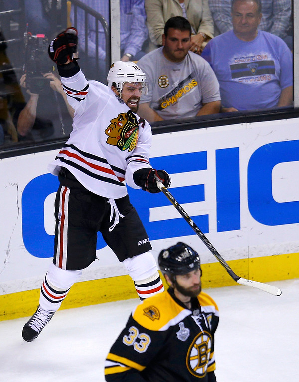 . Chicago Blackhawks\' Patrick Sharp celebrates his goal as Boston Bruins\' Zdeno Chara skates away during the third period in Game 4 of their NHL Stanley Cup Finals hockey series in Boston, Massachusetts, June 19, 2013. REUTERS/Brian Snyder