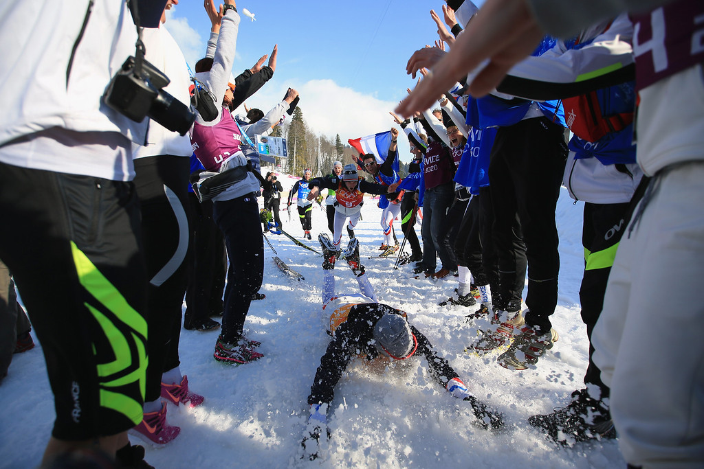 . Robin Duvillard (front) and Jean Marc Gaillard of France dive in the snow to celebrate winning the bronze medal after the Cross Country Men\'s 4 x 10 km Relay during day nine of the Sochi 2014 Winter Olympics at Laura Cross-country Ski & Biathlon Center on February 16, 2014 in Sochi, Russia.  (Photo by Richard Heathcote/Getty Images)