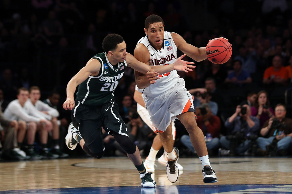 . Malcolm Brogdon #15 of the Virginia Cavaliers handles the ball Travis Trice #20 of the Michigan State Spartans during the regional semifinal of the 2014 NCAA Men\'s Basketball Tournament at Madison Square Garden on March 28, 2014 in New York City.  (Photo by Bruce Bennett/Getty Images)