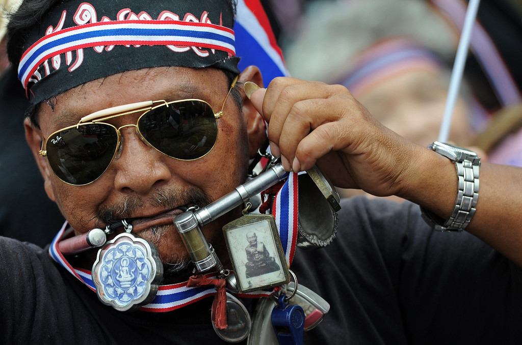 . A Thai opposition protester bites a necklace carrying amulets during a rally at the occupied Finance Ministry in Bangkok on November 26, 2013.    AFP PHOTO/Christophe ARCHAMBAULT/AFP/Getty Images