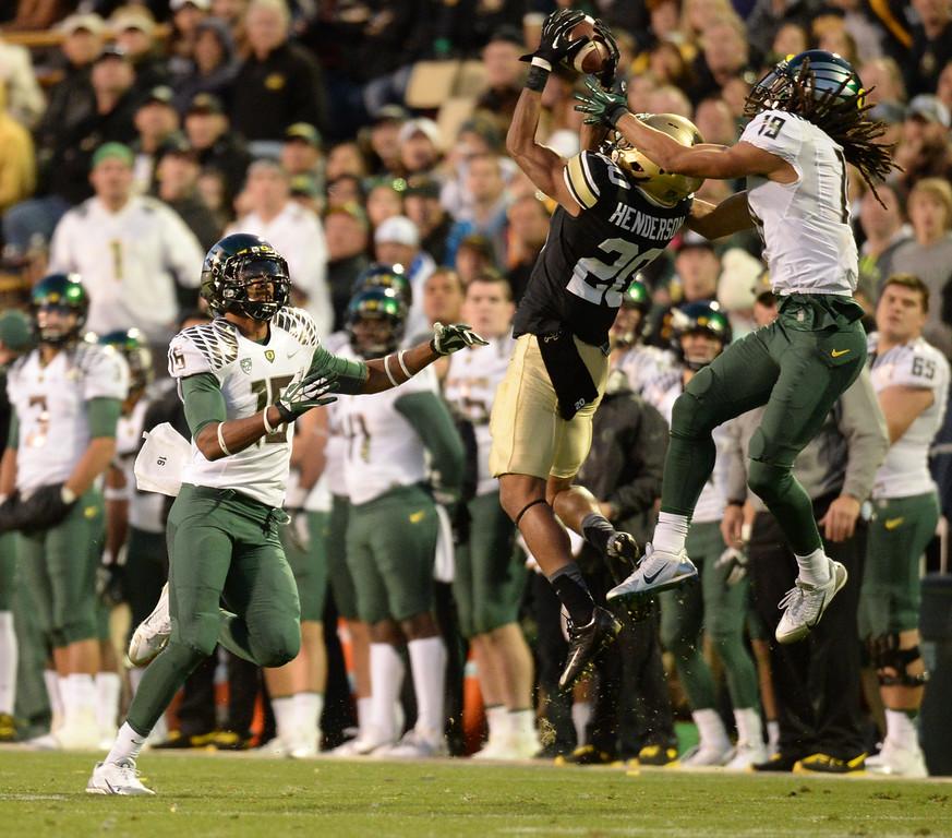 . Greg Henderson of University of Colorado (20) intercepts the ball between Daryle Hawkins (16) and Eric Dungy (19) of University of Oregon in the 4th quarter of the game at Folsom Field. Boulder, Colorado. October 5, 2013. Oregon won 57-16. (Photo by Hyoung Chang/The Denver Post)