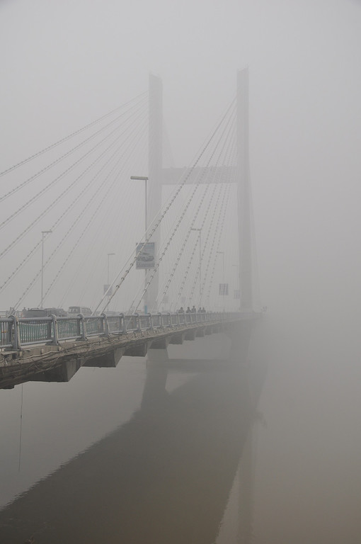 . Vehicles are driven along a bridge on the Songhua River as heavy smog engulfs the city on October 21, 2013 in Jilin, China. Expressways, schools and an airport remain closed as heavy smog continues to disrupt northeast China.  (Photo by ChinaFotoPress/Getty Images)