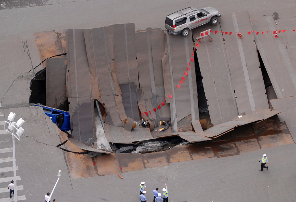 . Policemen check a collapsed section of a crossroad in Hefei, Anhui province August 8, 2009. A taxi and a few motorbikes fell into the hole, local media reported. REUTERS/China Daily