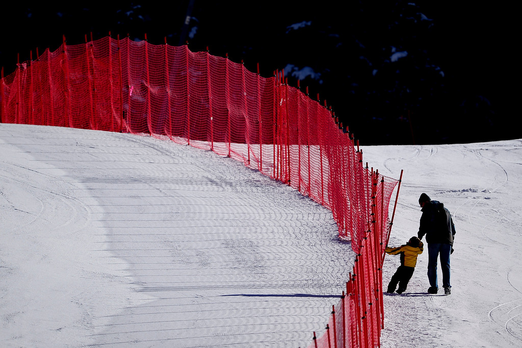 . A man and a boy walk uphill during the middle stages of downhill training for the Women\'s World Cup downhill on Tuesday, November 26, 2013. (Photo by AAron Ontiveroz/The Denver Post)
