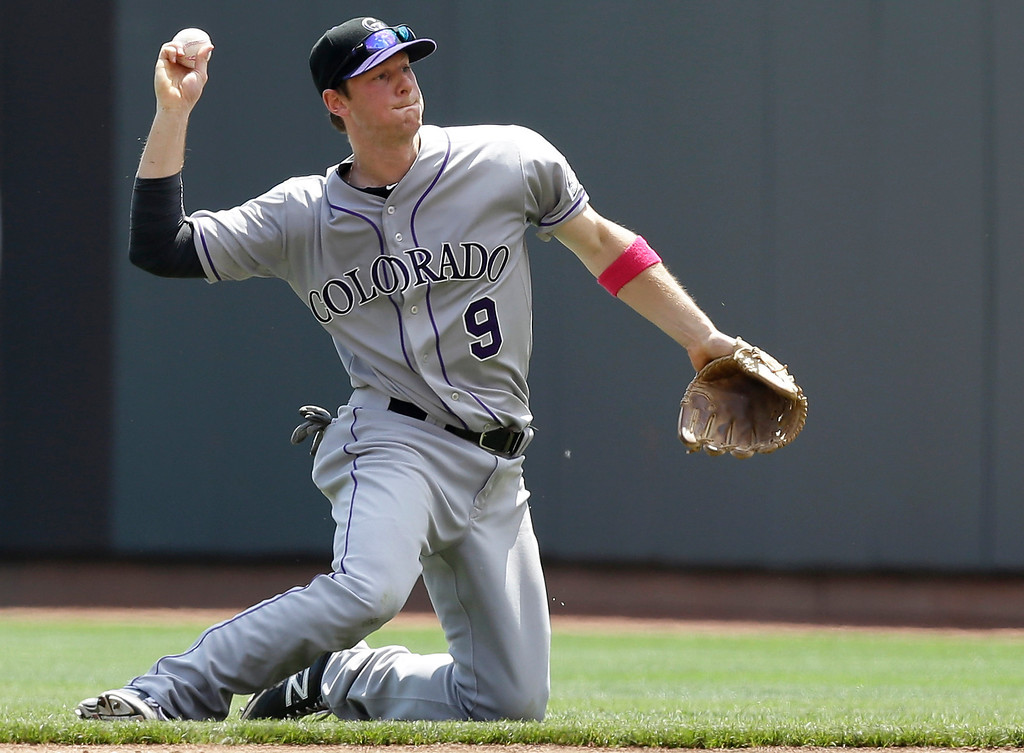. Colorado Rockies second baseman DJ LeMahieu throws to first for the out after fielding a ground ball hit by Cincinnati Reds\' Joey Votto in the fourth inning of a baseball game, Sunday, May 11, 2014, in Cincinnati. (AP Photo/Al Behrman)