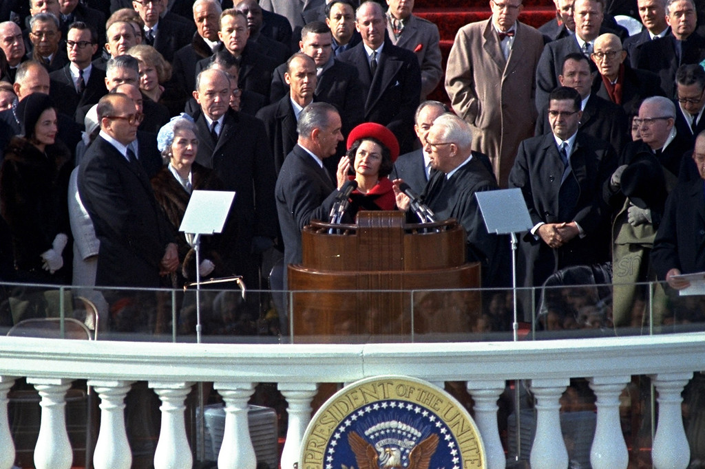 . A distant view of Lyndon Johnson, shown taking the oath of office, during the inauguration ceremonies in front of the Capitol Building in Washington, D.C., on Jan. 20, 1965. Administering the oath is Chief Justice Earl Warren, right. Holding the bible at center is Lady Bird Johnson, beginning a new tradition. (AP Photo)