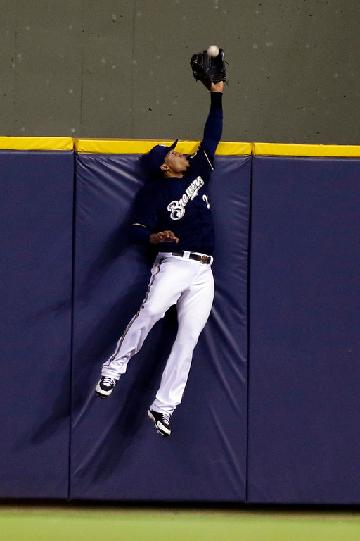 . Milwaukee Brewers\' Carlos Gomez takes a home run away from Colorado Rockies\' Carlos Gonzalez during the sixth inning of a baseball game, Wednesday, April 3, 2013, in Milwaukee. (AP Photo/Jeffrey Phelps)