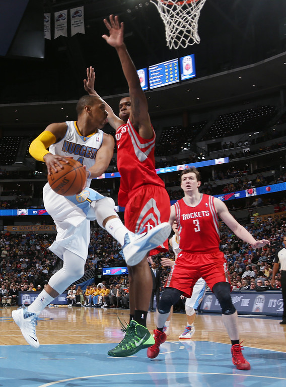 . Denver Nuggets guard Randy Foye, left, drives the lane for a shot as Houston Rockets forward Terrence Jones, center, and center Omer Asik, of Turkey, cover in the third quarter of the Nuggets\' 123-116 victory in an NBA basketball game in Denver on Wednesday, April 9, 2014. (AP Photo/David Zalubowski)