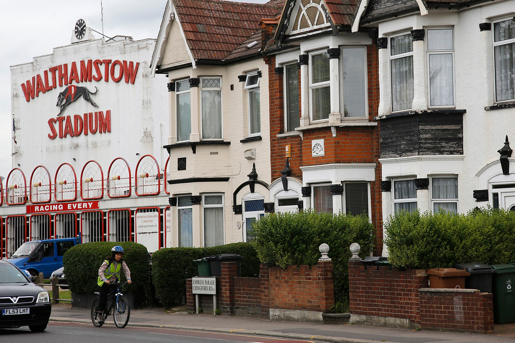 . A cyclist passes the facade of the now-derelict Walthamstow Stadium, owned by property developers L&Q, in Walthamstow, east London May 31, 2012. Blaming track closures in Reading, Walthamstow, Hull, Portsmouth, Coventry and Oxford, the Greyhound Board of Great Britain say that the number of professional trainers has fallen by 129 in the last five years, from 510 in 2008 to 381 today. Picture taken May 31, 2012. REUTERS/Chris Helgren