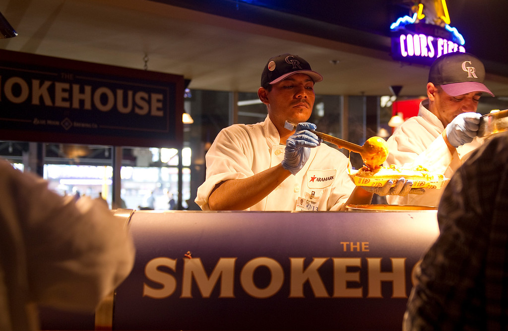 . Moe Jamoun loads on the cheddar at the The Smokehouse at the The Blue Moon Brewing Co. at the SandLot at the park on May 3, 2013 before the Rockies game. (Photo By Cyrus McCrimmon/The Denver Post)