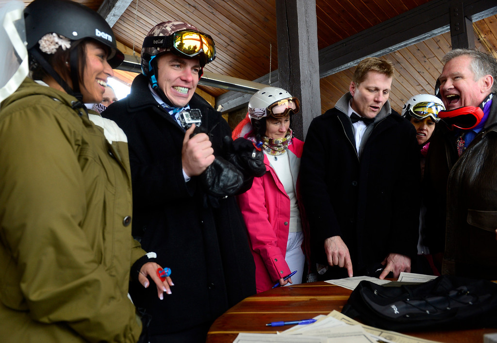 """. GEORGETOWN, CO - FEBRUARY 14: The minister who officiated the ceremony, Harry Heilman, right, laughs out loud as he tells couple Charles Mead, second from left, and Adriana Beutel, left, that it\'s official now that they have signed the marriage license. Dozens of couples decided to say \""""I do\"""" for the first time or repeat their wedding vows on Valentines Day at the 23rd Annual Mountaintop Matrimony at Loveland Basin ski area. The couples hovered together to keep warm with white-out conditions at 12, 050 feet just outside the Ptarmagin Roost cabin at the top of chairlift #2 with the minister Harry Heilman officiating. (Photo by Kathryn Scott Osler/The Denver Post)"""
