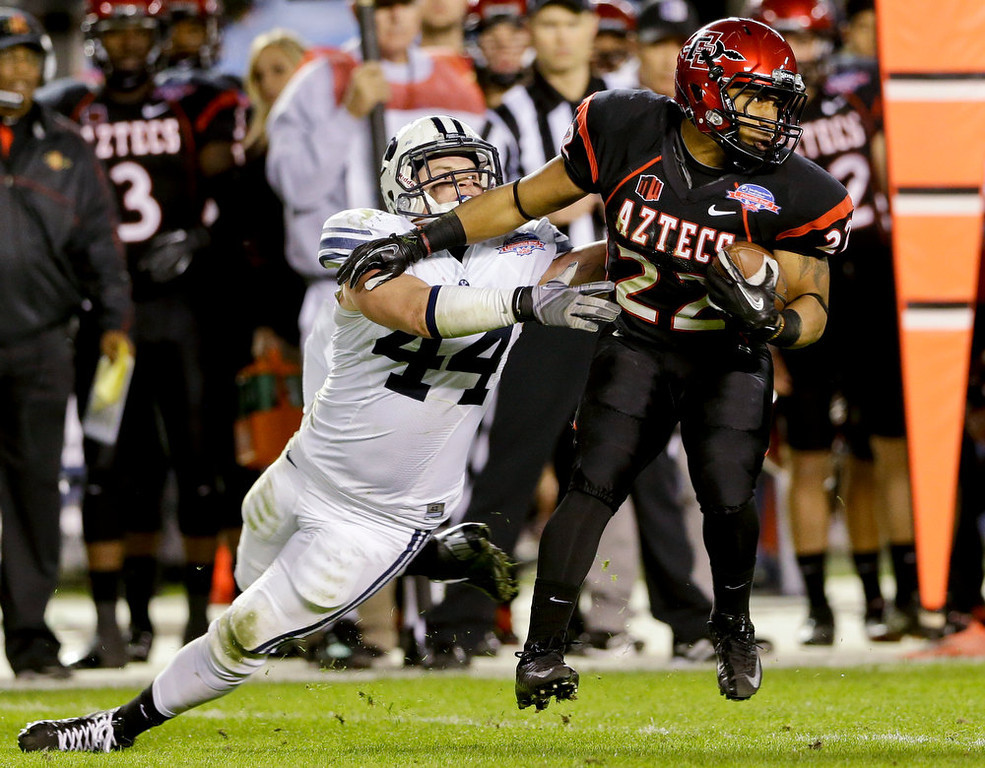 . San Diego State running back Chase Price breaks a tackle by BYU\'s Brandon Ogletree after catching a pass during the first half of the Poinsettia Bowl NCAA college football game, Thursday, Dec. 20, 2012, in San Diego. (AP Photo/Lenny Ignelzi)
