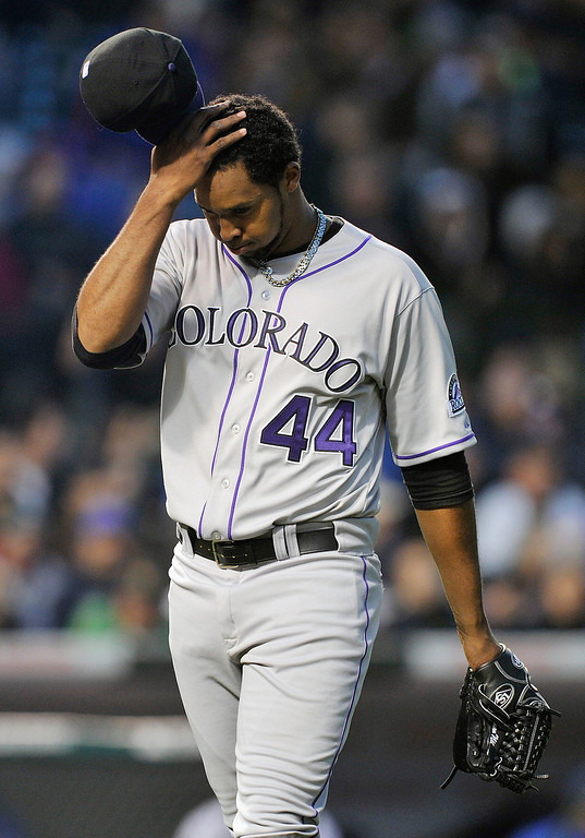 . Colorado Rockies\' Juan Nicasio  stretches his head after giving up three runs against the Chicago Cubs during the third inning of a baseball game Monday, May 13, 2013, in Chicago. (AP Photo/Jim Prisching)